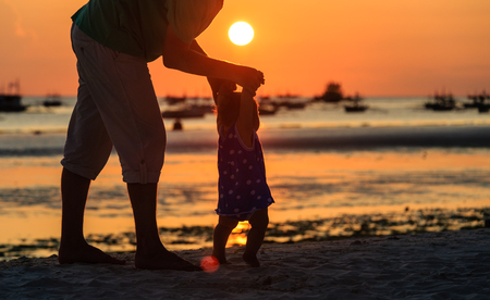 fathers  day: Silhouette of father and little daughter on the beach