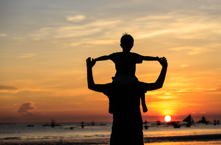 father's: father and son on sky at sunset beach Stock Photo