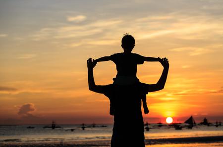 ni�os felices: padre e hijo en el cielo en la playa de la puesta del sol Foto de archivo