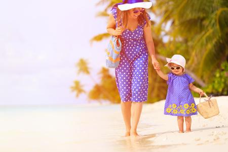 petite fille avec robe: m�re et sa petite fille mignonne marchant sur la plage tropicale