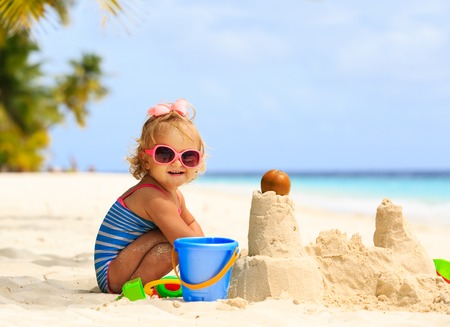 cute little girl playing with sand on tropical beach Stockfoto