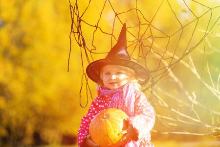trick or treating: little girl in halloween costume in autumn park, kids trick or treating