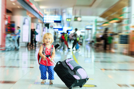 mochila viaje: ni�a con maleta de viaje en el aeropuerto, viajan ni�os