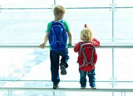 kleine jongen en peuter meisje op zoek naar vliegtuigen in de luchthaven, reizen kinderen