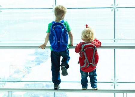 little boy and toddler girl looking at planes in the airport, kids travel Foto de archivo