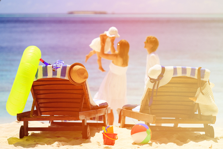 happy holiday: chairs on tropical beach, family beach vacation concept