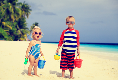 lindo: cute little boy and toddler girl play with sand on tropical beach