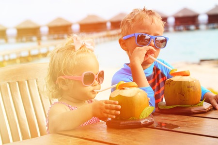 resort: little boy and toddler girl drinking coconut cocktail on tropical beach resort, kids luxury travel Stock Photo
