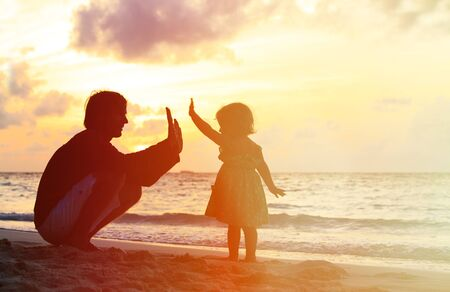 parent child: Father and little daughter playing silhouettes on beach at sunset