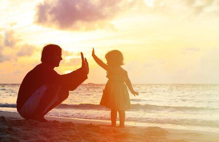 padres hablando con hijos: Padre y peque�a hija que juegan las siluetas en la playa al atardecer Foto de archivo