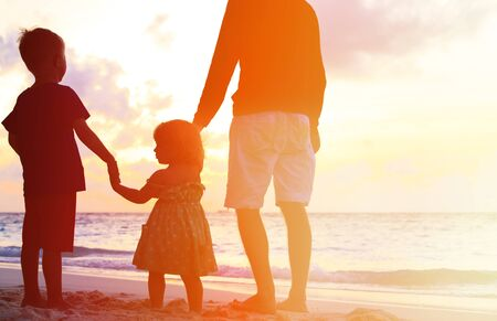 family support: silhouette of father and two kids walking on beach at sunset Stock Photo