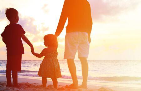 apoyo familiar: silueta del padre y dos ni�os caminando en la playa al atardecer