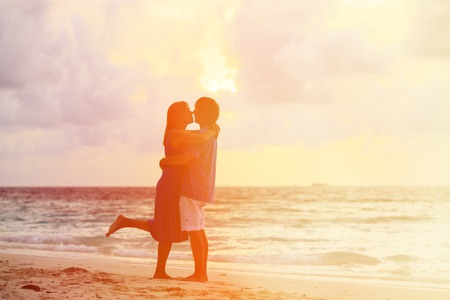 romantic beach: Happy young romantic couple on the beach at sunset Stock Photo