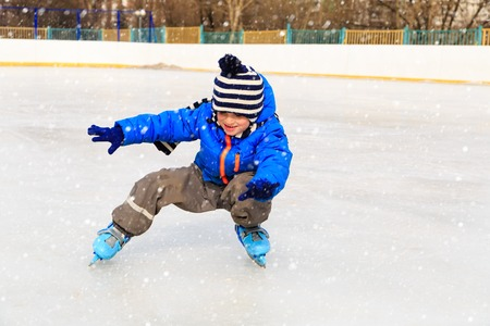 aprendizaje: niño lindo aprender a patinar en la nieve del invierno Foto de archivo