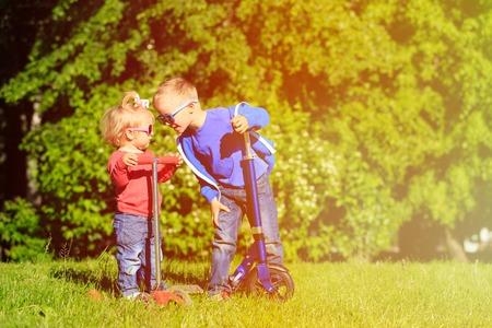 caras: ni�o y ni�a linda para andar en monopat�n en el parque de verano