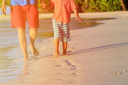 footprints in the sand: father and son walking on beach leaving footprint in the sand, family beach travel Stock Photo