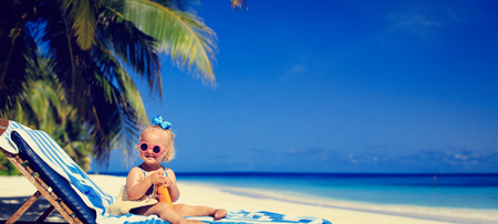 little girl swimsuit: cute little girl with sunblock cream on beach, wide panorama Stock Photo