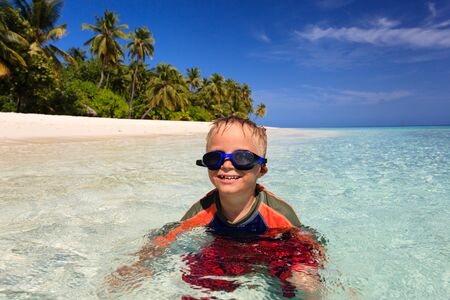 little boy swimming: happy little boy swimming on tropical beach vacation
