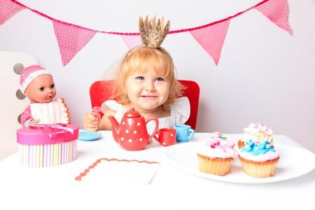 gelukkig schattig meisje met snoep en poppen op verjaardagsfeestje