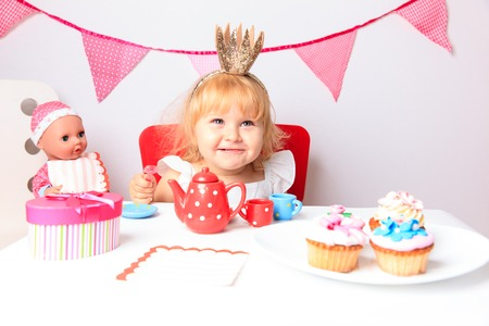 birthday party kids: happy cute little girl  with sweets and dolls at birthday party