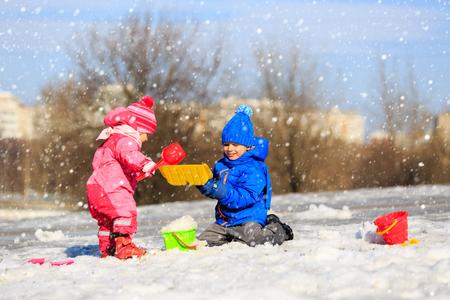 sweet baby girl: little boy and girl digging snow in winter, kids winter activities