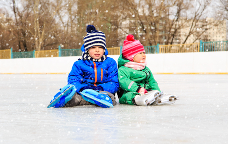 ice cold: little boy and girl sitting on ice with skates, kids winter sport