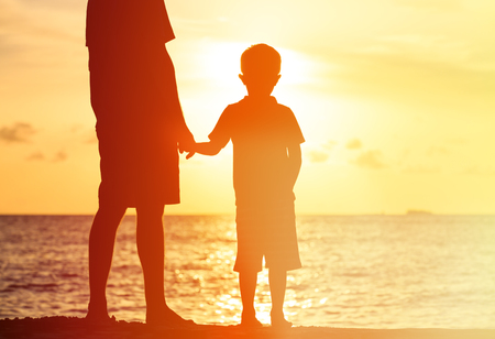holding back: silhouettes of father and son holding hands at sunset sea