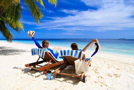 vacation destination: happy couple relax on a tropical sand beach