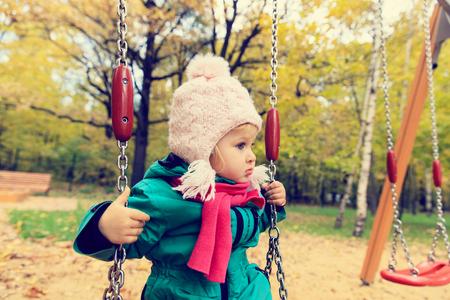 bebes niñas: la niña linda que se divierte en el oscilación en el día de otoño