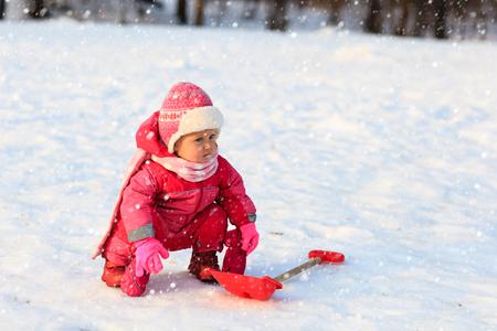dig: cute little toddler girl dig in winter snow, kids winter fun