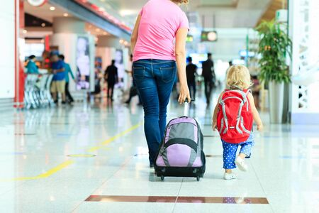 mujer con maleta: mother and little daughter walking in the airport, family travel