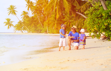 adult beach: father and two kids collecting shells on tropical beach Stock Photo