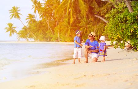 petit bonhomme: père et deux enfants ramasser des coquillages sur la plage tropicale