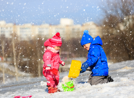 baby girls: little boy and girl digging snow in winter, kids winter activities
