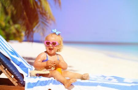 little girl beach: cute little girl with sunblock cream on tropical beach