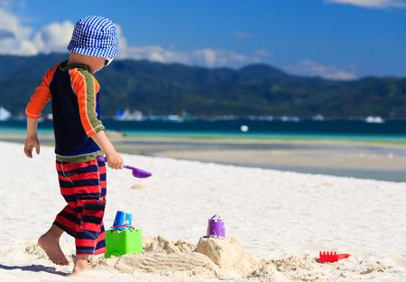 sandcastle: child building sandcastle on tropical sand each