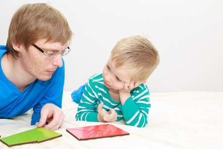 early education: father and son playing with puzzle, early education concept Stock Photo