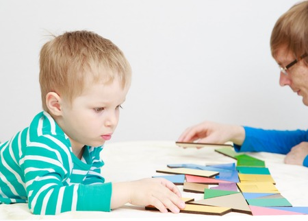 early education: child playing with puzzle, early education concept Stock Photo