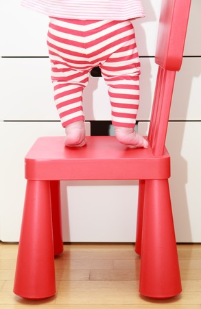 baby chair: child feet on baby chair, concept of danger, risk and parent responsibility Stock Photo