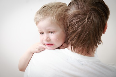 disobedient child: father comforting her crying little son - parenthood concept