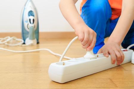 enchufe: jugando con la electricidad niño, el concepto de seguridad niños Foto de archivo
