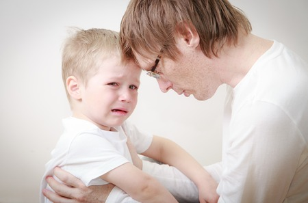 man crying: father comforting her crying little son - parenthood concept