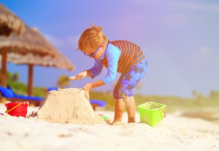 children sandcastle: little boy building sandcastle on tropical sand beach