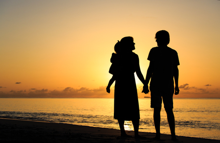 water concept: Happy family together, romantic couple with little child at sunset tropical beach Stock Photo