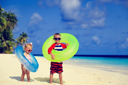 little: cute little boy and toddler girl play on tropical beach Stock Photo