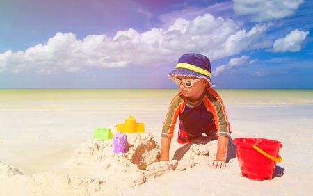sandcastle: little boy building sandcastle on tropical sand beach