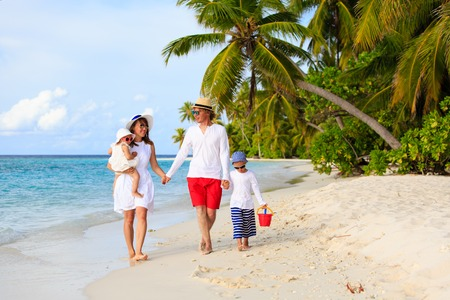 vacaciones en la playa: Familia joven con dos ni�os caminando en la playa tropical, vacaciones familiares en la playa