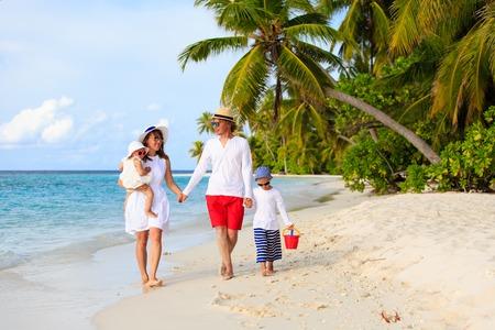 Jong gezin met twee kinderen lopen op tropisch strand, familie strand vakantie