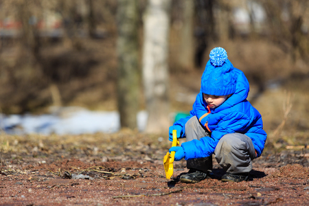 interst: little boy plaing in spring puddle outdoors, kids outdoor activities Stock Photo