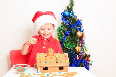 cute house: little boy in Santas hat building gingerbread house, christmas concept